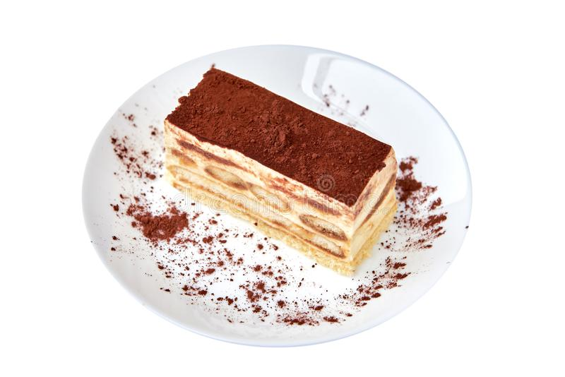 Postre de la torta del Tiramisu con cacao en una placa de la porcelana en el fondo blanco imágenes de archivo libres de regalías
