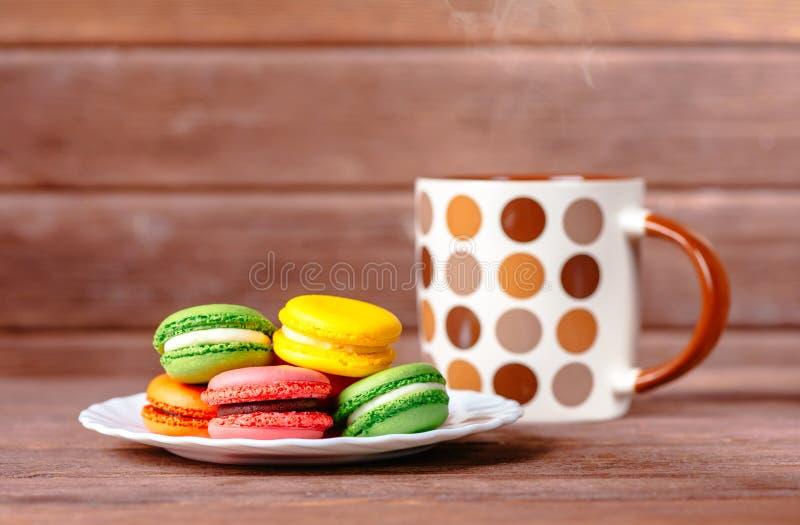 Postre de Macarons y bebida caliente foto de archivo