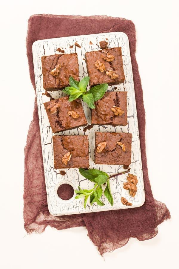 Postre del chocolate dulce del brownie con las nueces y las hojas significadas en tablero retro con el espacio de la copia en fon stock de ilustración