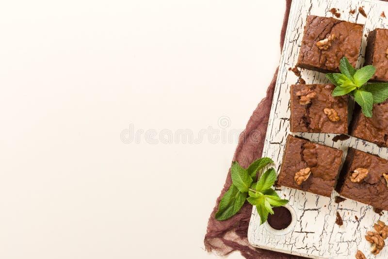Postre del chocolate dulce del brownie con las nueces y las hojas significadas en tablero retro con el espacio de la copia en fon ilustración del vector