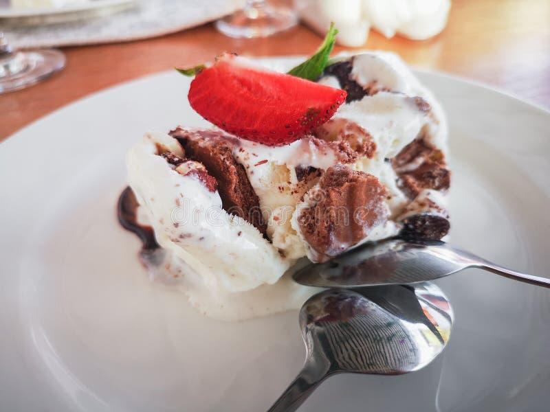 Postre del helado de vainilla, doused con el chicolade con las fresas y las hojas de menta en una placa blanca Dispositivos de ac fotografía de archivo