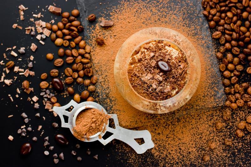 Postre del Tiramisu con los granos del chocolate, del cacao y de café en un bla fotos de archivo