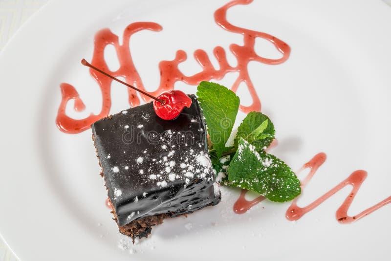 Postre delicioso Un pedazo de torta de chocolate con el polvo, la cereza y la menta Marco horizontal fotografía de archivo