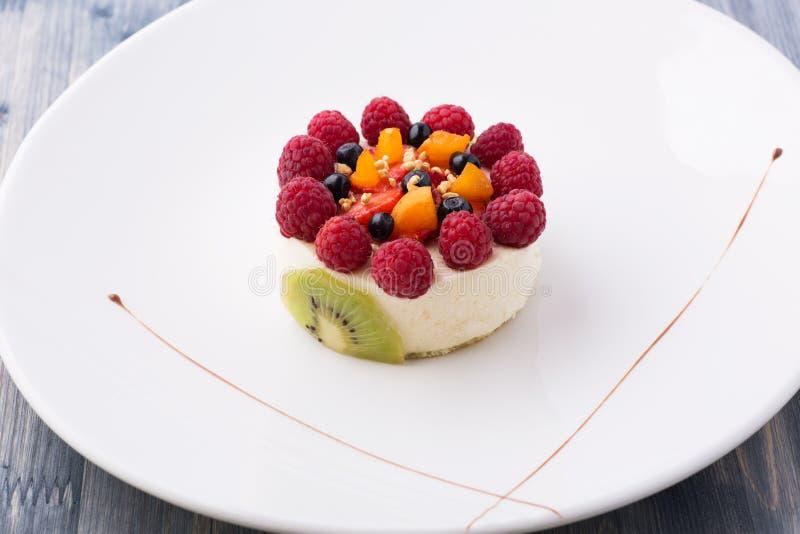 Postre dulce con los rasberries, el kiwi y la crema wheapped imagenes de archivo