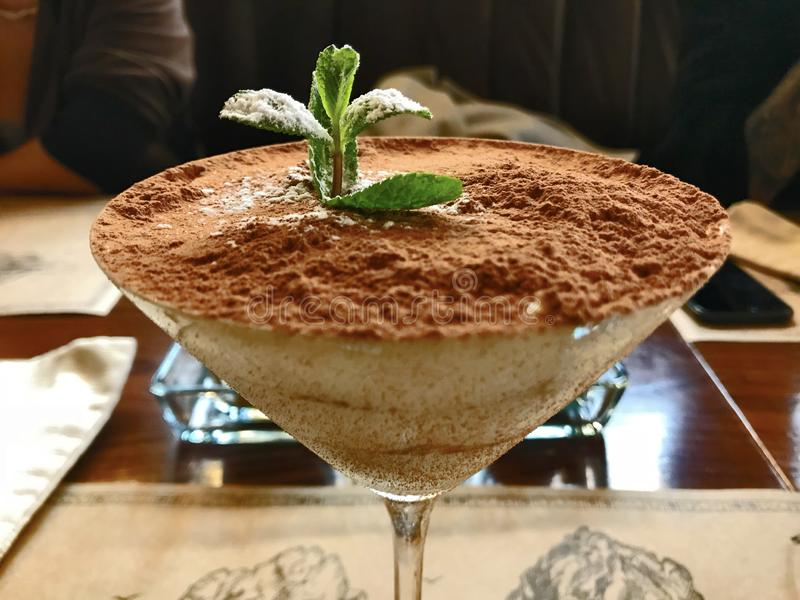 Postre dulce del tiramisu de la elegancia con la menta en el vidrio de martini imagen de archivo