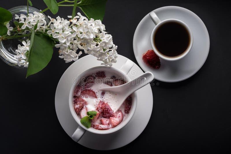 Postre, fresa con crema y rebanada de la menta, placa blanca, taza de café, fondo negro, visión superior imagen de archivo