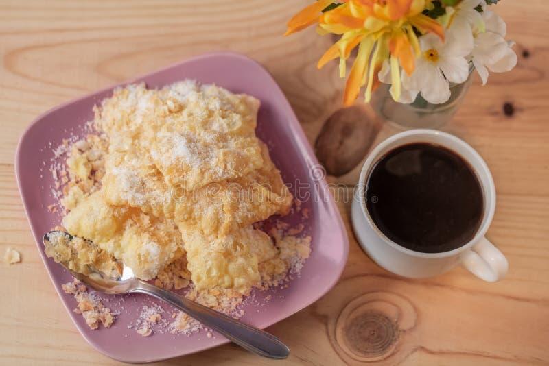 Postre Galletas curruscantes Crackled con el azúcar en una placa y una taza de café en una tabla rústica imagen de archivo libre de regalías