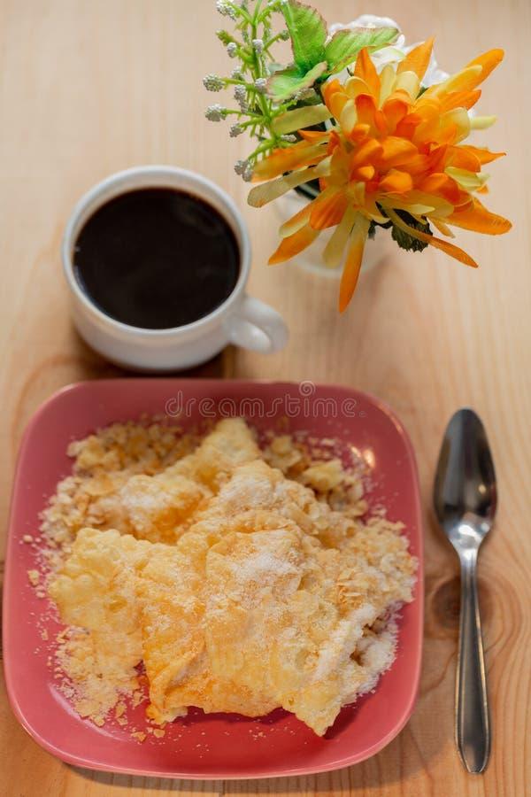 Postre Galletas curruscantes Crackled con el az?car en una placa y una taza de caf? en una tabla de madera foto de archivo