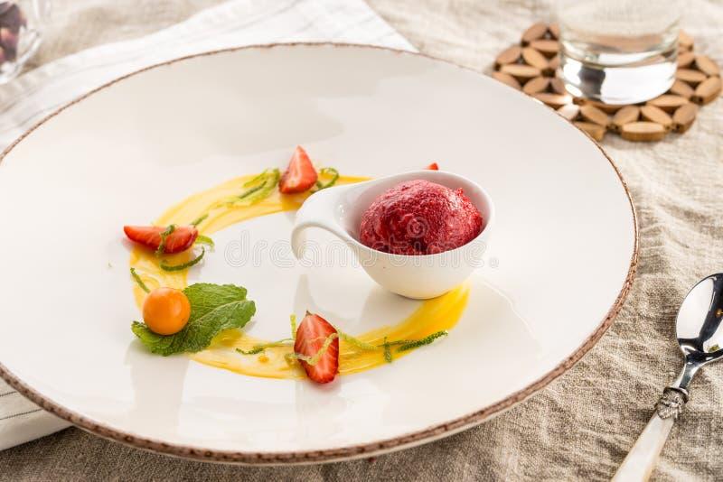 Postre gastrónomo elegante con el helado y la fruta de fresa servidos en la placa blanca en el restaurante imágenes de archivo libres de regalías
