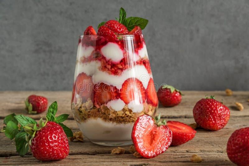 Postre helado del yogur de la fresa con el granola, la menta y las bayas frescas en un vidrio en la tabla de madera rústica Alime imagenes de archivo