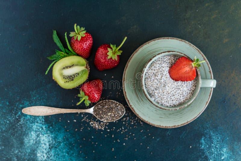 Postre hermoso y sabroso con un kiwi, una fresa y semillas de un chia imagen de archivo