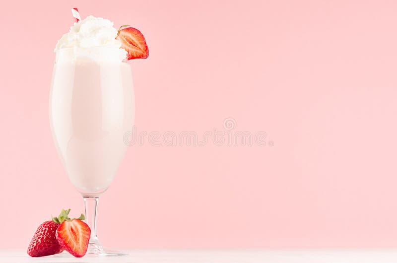 Postre ligero exquisito de la fresa de la leche con la baya jugosa de la rebanada, crema azotada, paja en fondo rosado elegante m fotos de archivo libres de regalías