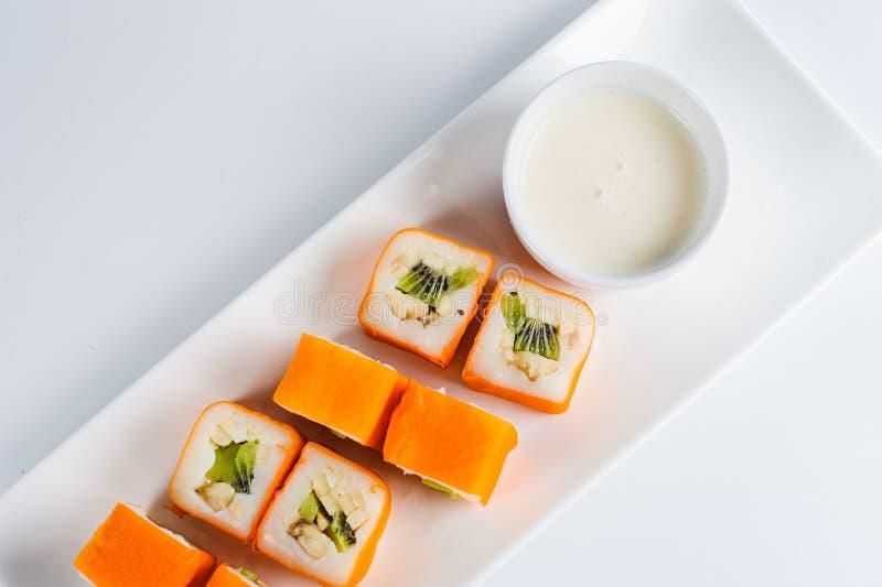 Postre Maki Sushi - ruede con la diversa fruta en pudín de arroz y el coco forma escamas fotos de archivo