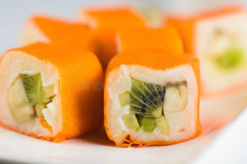 Postre Maki Sushi - ruede con la diversa fruta en pudín de arroz y el coco forma escamas fotografía de archivo
