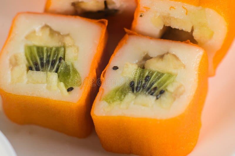 Postre Maki Sushi - ruede con la diversa fruta en pudín de arroz y el coco forma escamas imagenes de archivo
