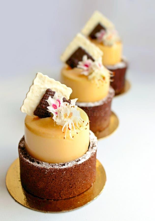 Postre mango-naranja el casarse de oro con las flores de la castaña de la primavera y la decoración de la servilleta del chocolat imagen de archivo libre de regalías