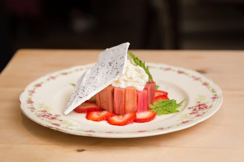 Postre moderno del pastel de queso del ruibarbo de la fresa con una oblea del merengue imagenes de archivo