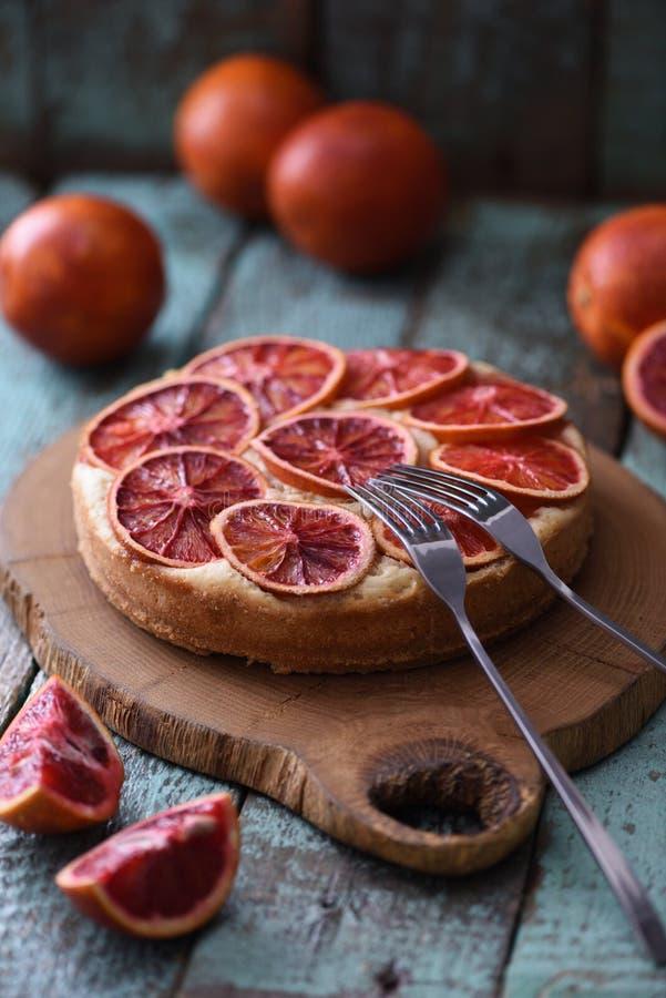 Postre nacional sabroso Torta de la naranja de sangre con las naranjas crudas en el oa foto de archivo