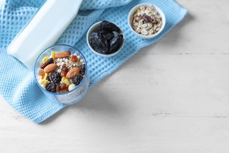 Postre sabroso de la harina de avena con las almendras y las frutas secadas en vidrio en fondo ligero foto de archivo libre de regalías
