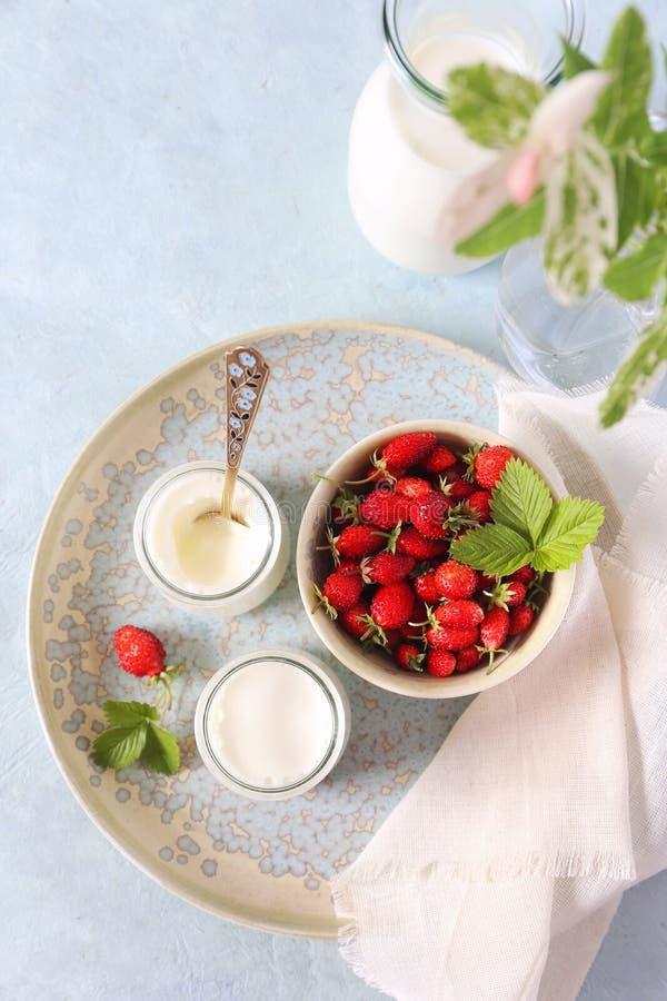 Postre sano de la leche: dos tarros de yogur fresco y de fresas salvajes foto de archivo