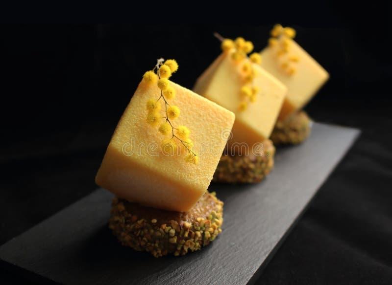 Postre texturizado amarillo brillante con las flores de la mimosa en base del pistacho en fondo negro fotos de archivo libres de regalías