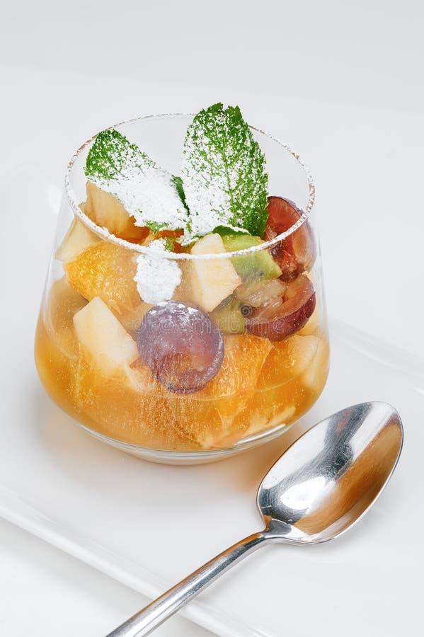 Postre vegetariano de la fruta con las hojas de la menta fresca y polvo del azúcar en foto vertical de la taza de cristal imágenes de archivo libres de regalías