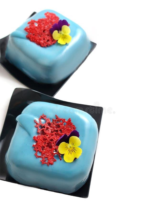 Postres cuadrados azules claros con crepé coralino rojo del cordón y la flor comestible imágenes de archivo libres de regalías
