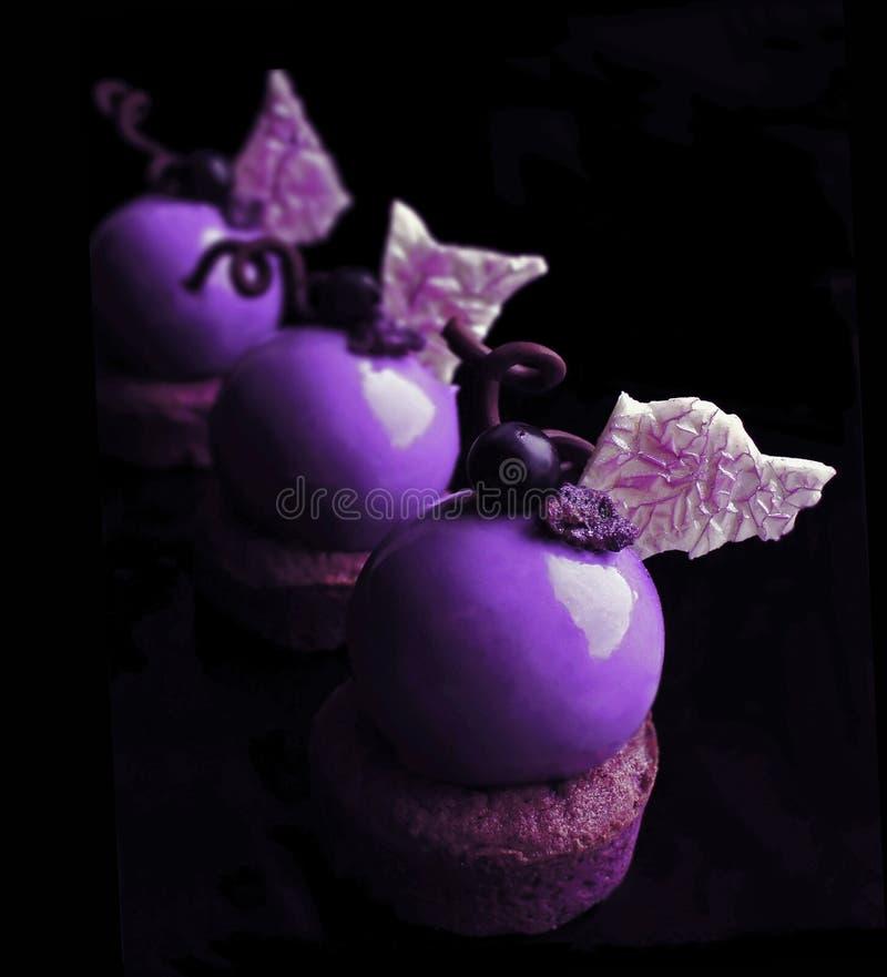 Postres púrpuras con las hojas y las uvas blancas del chocolate foto de archivo
