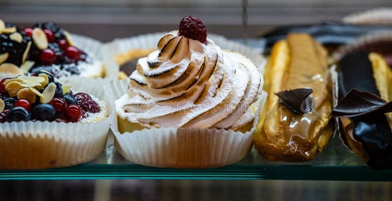 Postres, pasteles, tortas y diversos dulces en la cafetería y la ventana de la cafetería imagenes de archivo