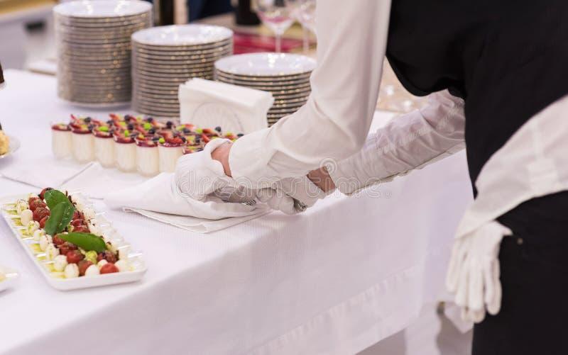 Postres y bocado magníficos en una tabla del día de fiesta Las manos del ` s del camarero en los guantes blancos fotografía de archivo