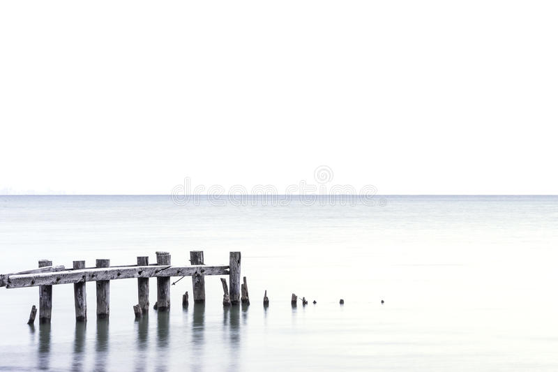 Posts of broken pier standing in a light blue lake, white sky ba royalty free stock images