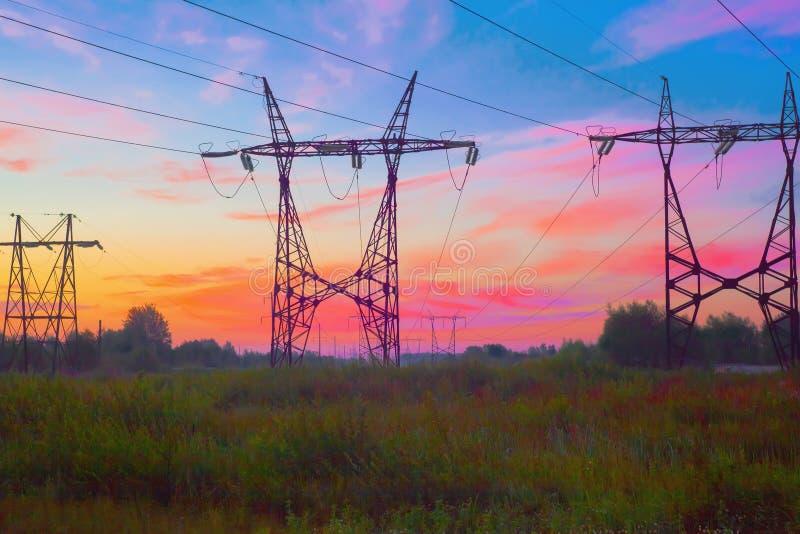 Posts de líneas eléctricas de alto voltaje, la visión de la barra de metal en la puesta del sol imagen de archivo