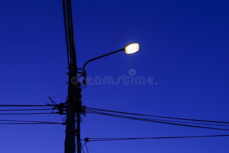 Posts de la electricidad y lámpara de la línea y de calle del cable en la noche foto de archivo