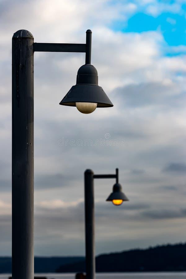 Posts de la lámpara de calle iluminados contra un cielo azul fotografía de archivo libre de regalías