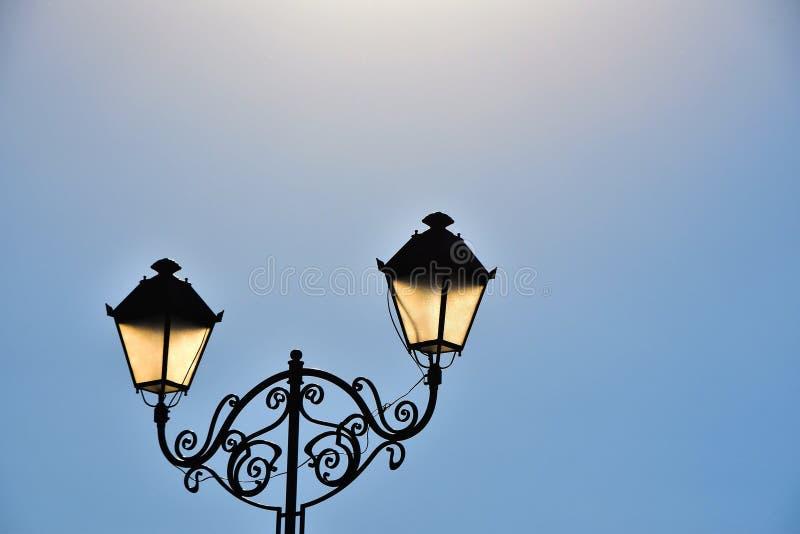 Posts dobles antiguos de la lámpara de la calle y cielo azul imagen de archivo libre de regalías