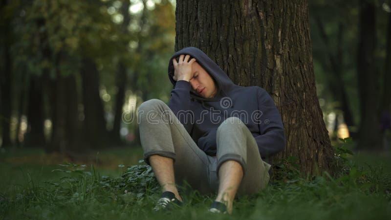 Postumi di una sbornia non sani dell'uomo in parco, sedentesi sotto l'albero dopo il buon partito, malattia fotografia stock libera da diritti