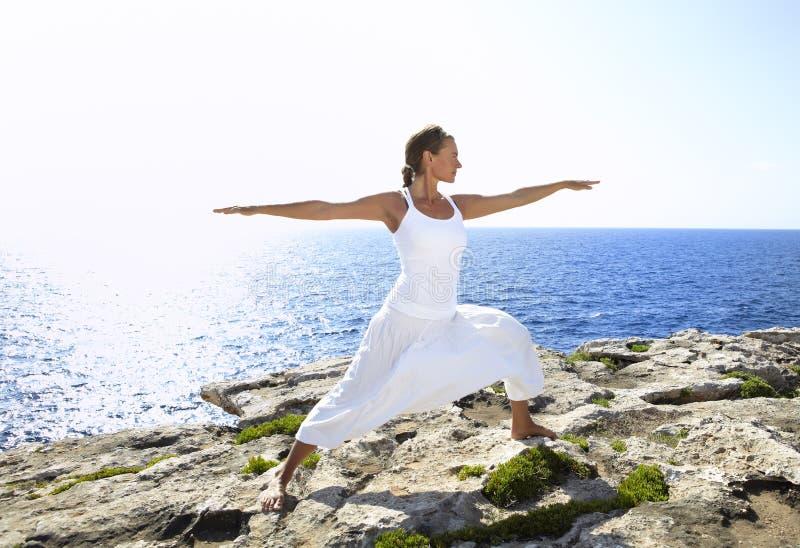 Postura da ioga em rochas perto do oceano imagens de stock