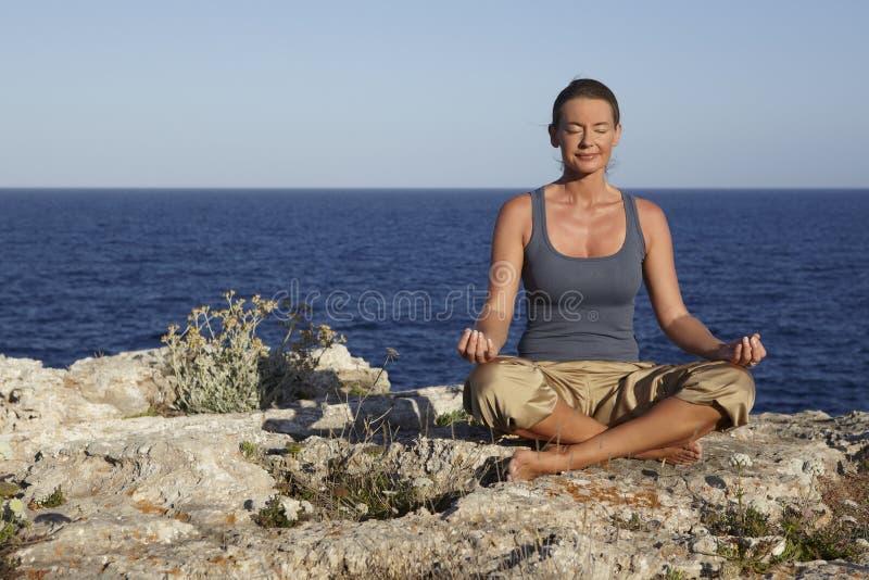 Postura da ioga em rochas perto do oceano imagem de stock royalty free