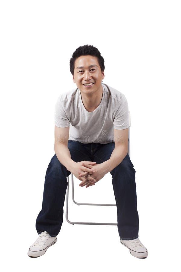 Postura de assento bem sucedida do homem novo imagem de stock