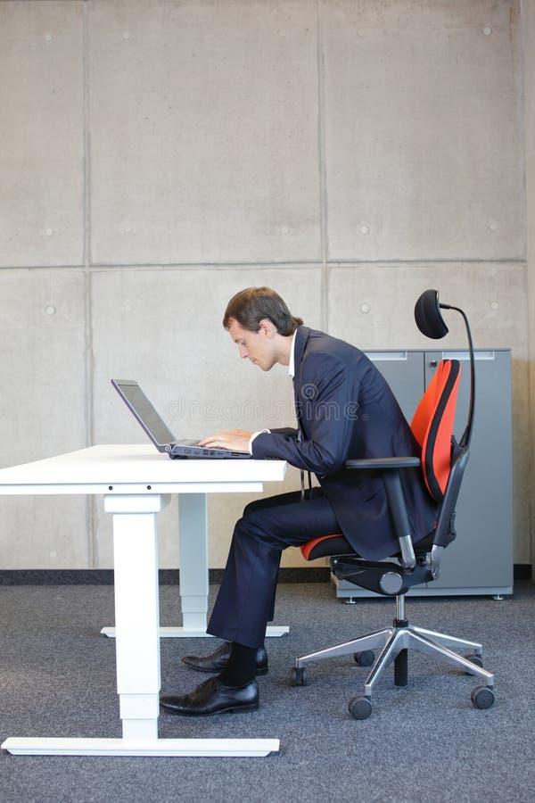 Postura de assento má no homem de negócio do portátil foto de stock