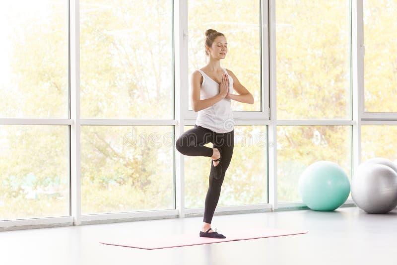 Postura del árbol Woamn que equilibra en una pierna y que hace yoga imagen de archivo