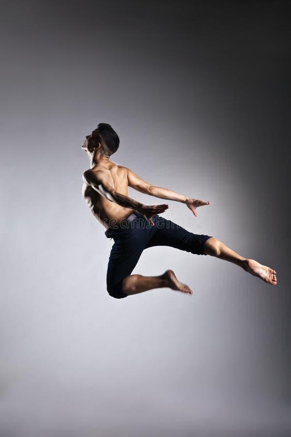 Postura ginástica do pulo do homem caucasiano no cinza fotos de stock royalty free