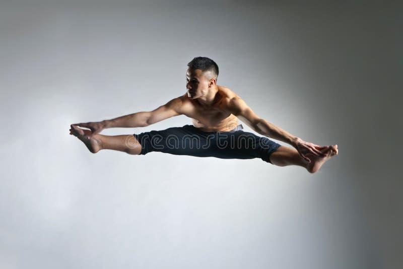 Postura ginástica do pulo do homem caucasiano no cinza imagem de stock
