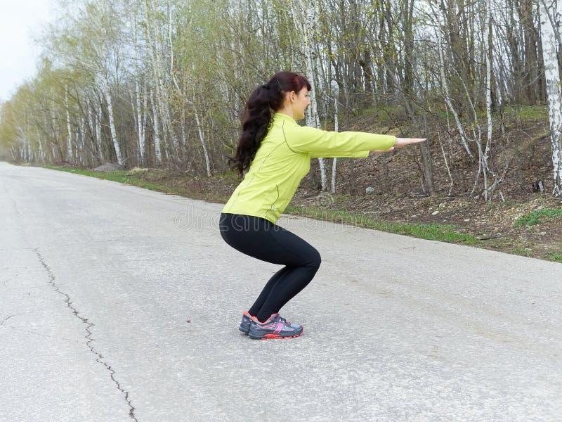 Posture accroupie de jeune femme dehors en nature photos stock