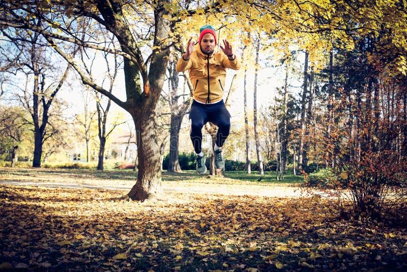 Posture accroupie de saut d'exercice d'homme Sur le mouvement photos stock
