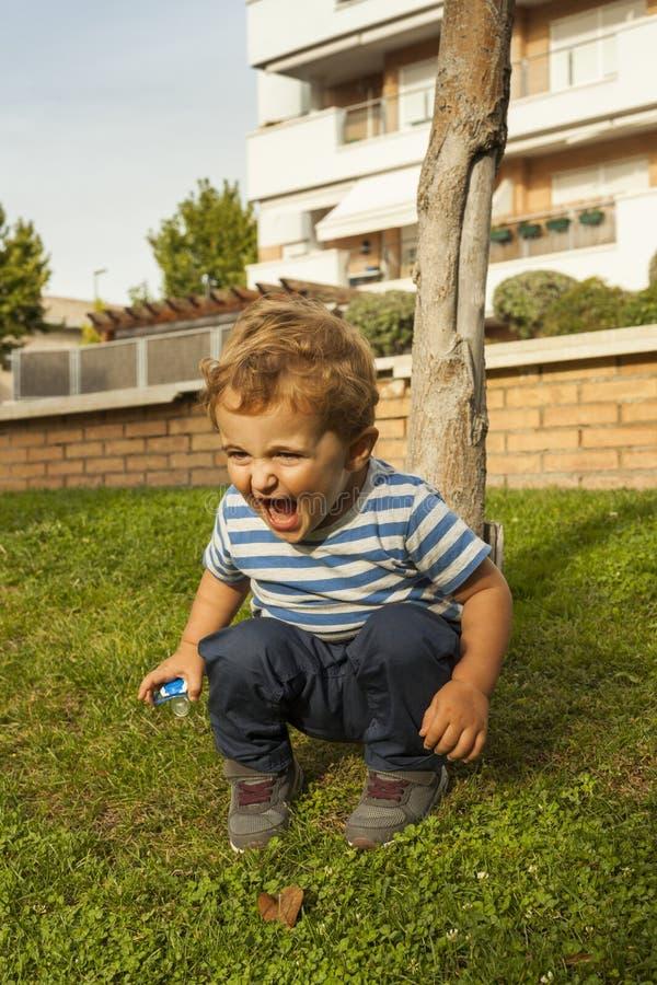 Posture accroupie souriante mignonne de bébé garçon de portrait de plein tir dans l'herbe images stock