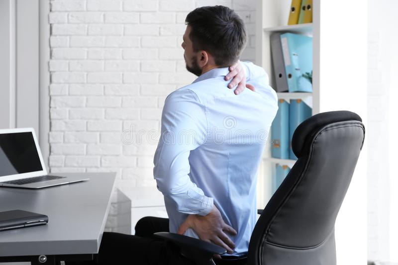 Posture concept. Man suffering from back pain while working with laptop royalty free stock photography
