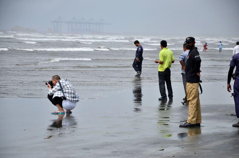 Postures accroupies chinoises d'homme avec la caméra prenant la photo à la Karachi Pakistan de l'eau de plage de vue de mer images libres de droits