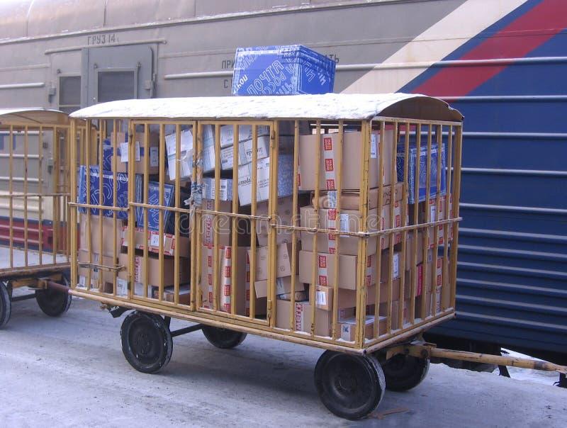 Postwagen mit Buchstaben und Paketen nahe der Auto geladenen russischen Posten Nowosibirsk-Station lizenzfreie stockbilder