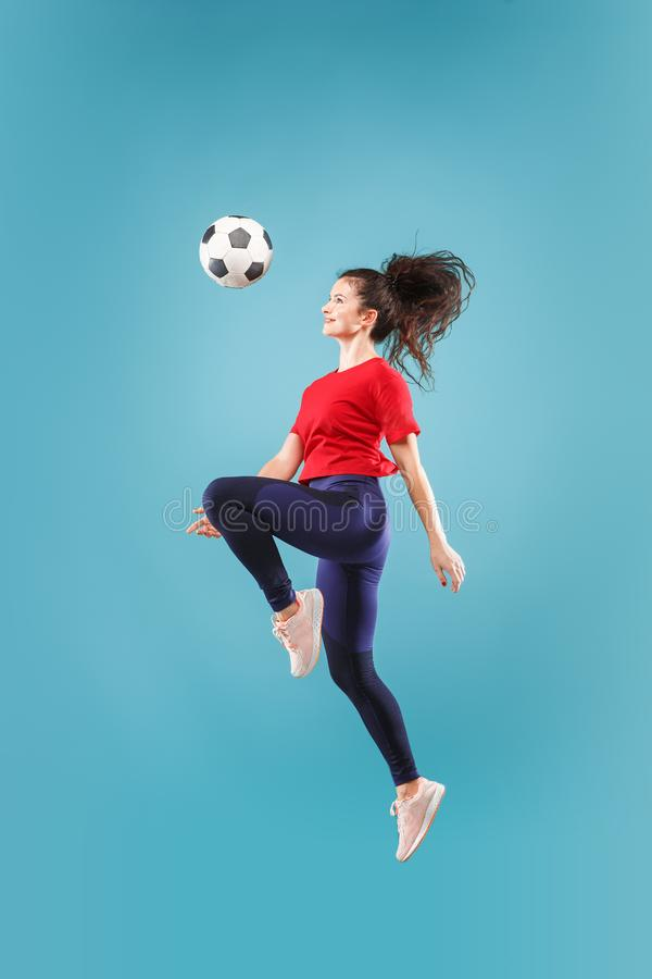 Posyła zwycięstwo Młoda kobieta jako piłka nożna gracza futbolu kopanie i doskakiwanie piłka przy studiiem na menchiach fotografia stock
